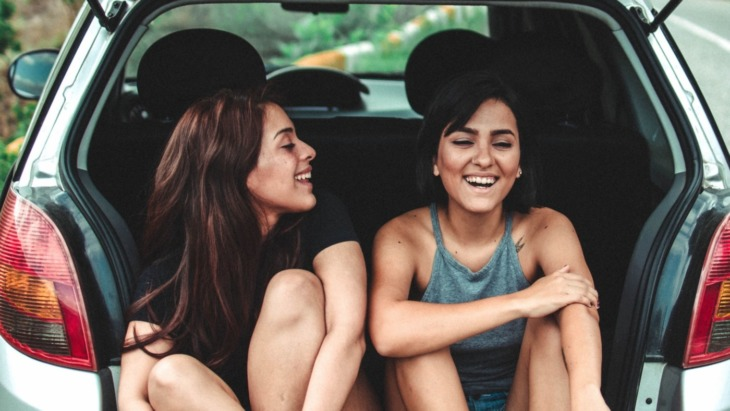 Road-tripping college students sit in the boot of their car.
