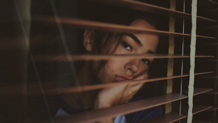 Isolation: a student peeks out of her blinds.