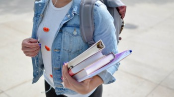 Physical vs digital. A student carries her books on campus.