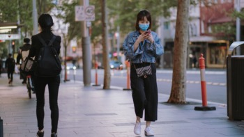 The new norm: a teen walks along the street wearing a face mask.