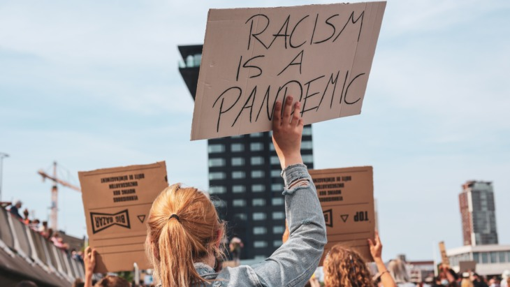 """Protestor holds sign which reads """"racism is a pandemic""""."""