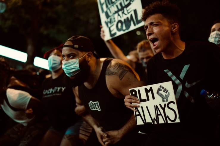 A man wears a mask at a BLM protest.