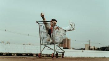 a woman sits in a shopping trolley