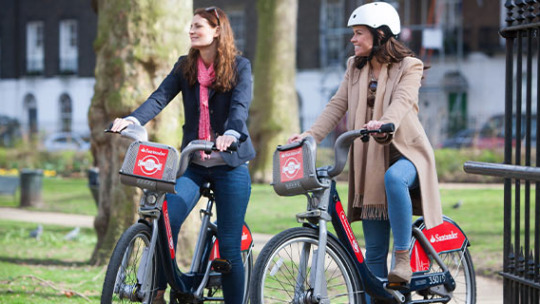 Two women ride on Santander Cycles.