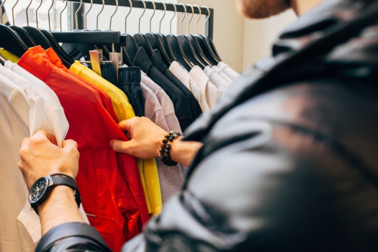 A man browses a rack of clothes