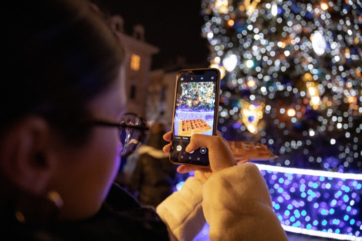 A woman takes a picture of a christmas tree