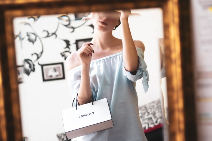 A woman holds a luxury fashion bag from the brand Chanel.