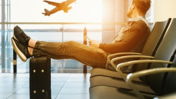 student sits in an airport watching a plane from the window