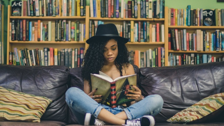 A girl sits and reads a book