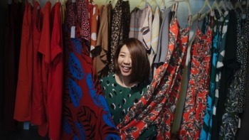 female stood under a rack of colourful garments