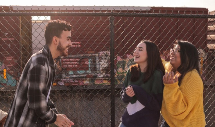 three students laughing in front of a wired fence