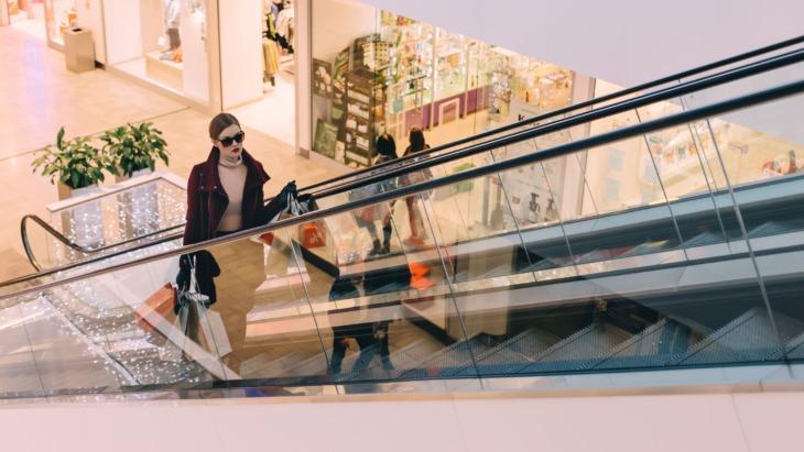 A woman rides an escalator in a shopping centre