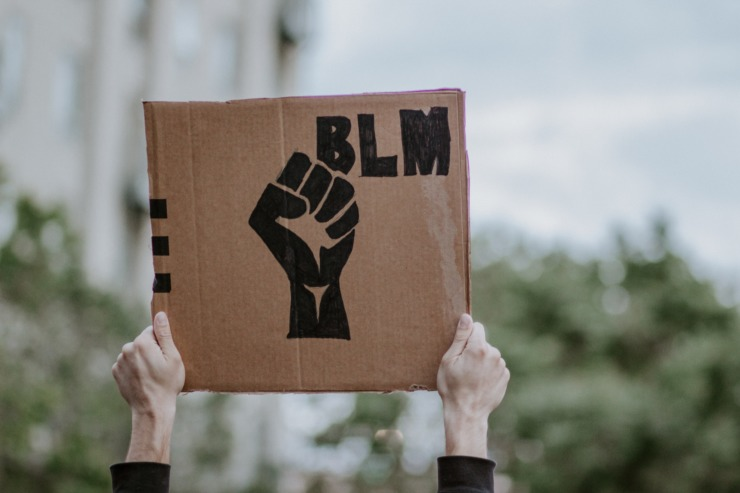 person holds a sign with BLM and a fist drawn on it