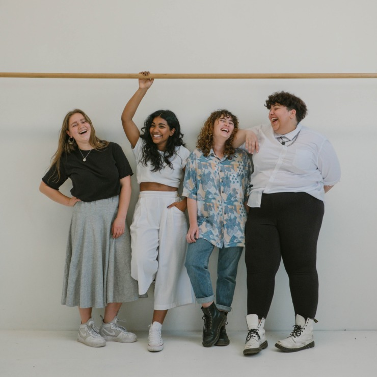 Four young people pose in stylish clothing
