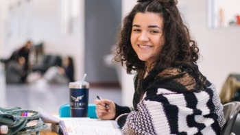 female student sat at a desk with pen and paper