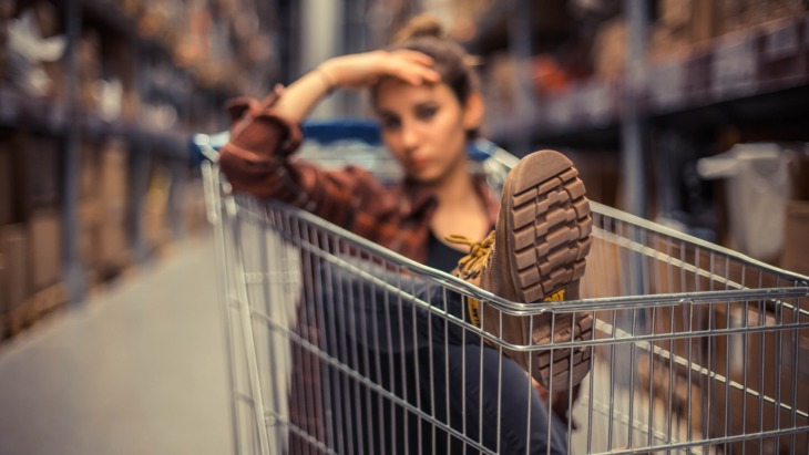Girl sitting in a trolley in a shop