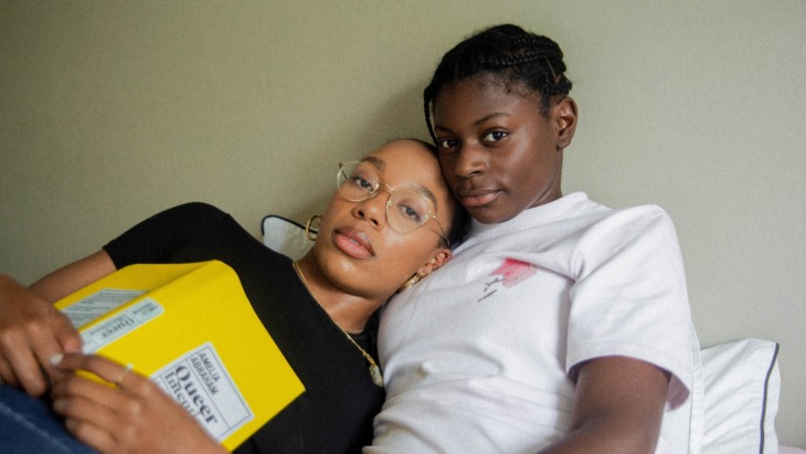 Two LGBTQ+ persons lying on a bed together