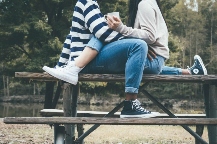 two people sat on a bench embracing