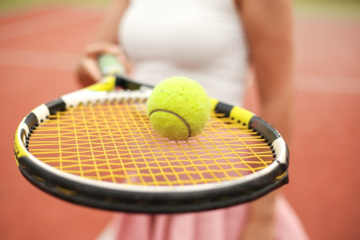 close up of a tennis racket and tennis ball