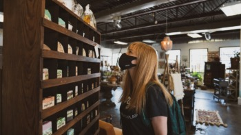 A girl browses in store, wearing a mask