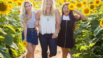 three young women laughing in a scene of sunflowers