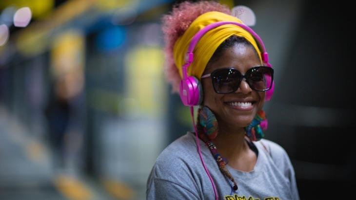 a woman smiles while listening to headphones