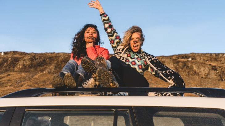 two girls sat on the top of a car