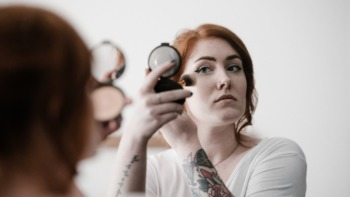 A woman applies makeup with a compact mirror