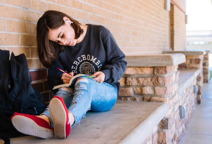 student sat on a bench writing in a book