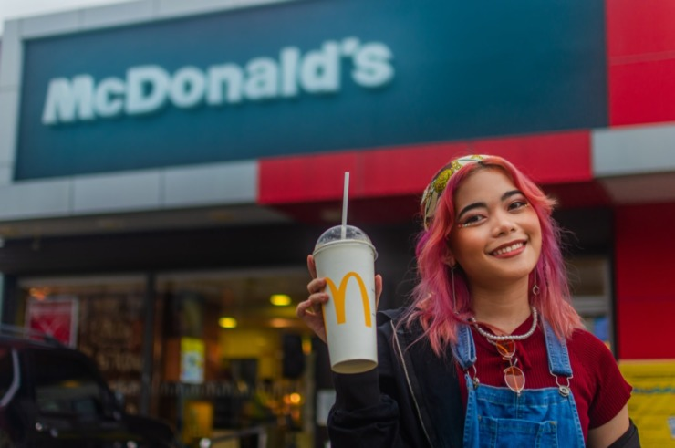 Girl with pink hair holding a McDonald's drink