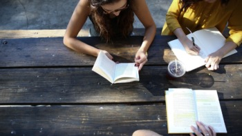 Three students reading outside on a bench
