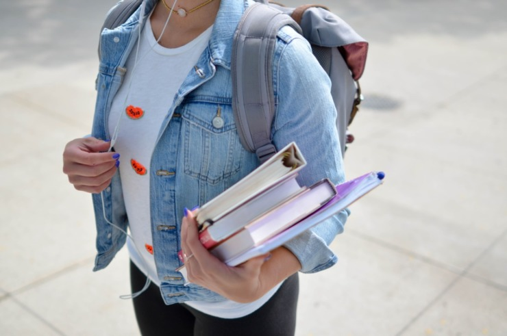 Student holding their binders and back pack