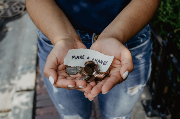 student holding coins with a sign saying 'make a change'