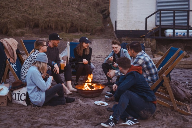 group of students sat round a fire on the beach