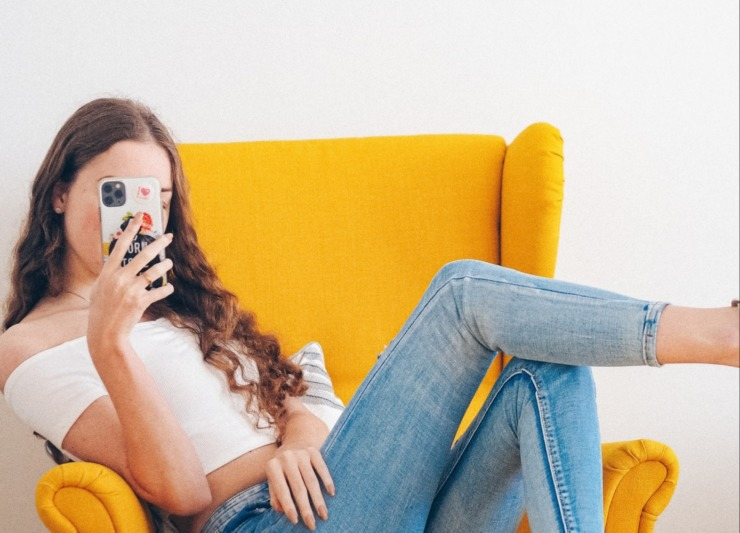 Student sat on a yellow chair taking a selfie
