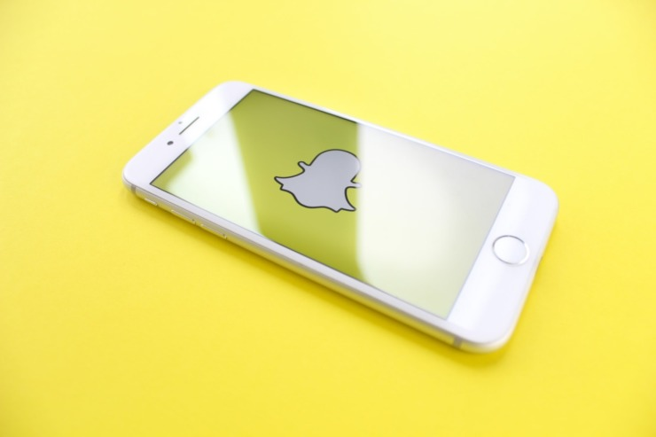 Iphone screen featuring the Snapchat Icon on a yellow background