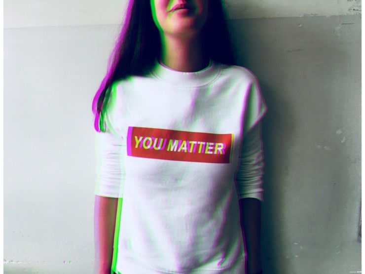 person wearing a white top that says 'you matter'