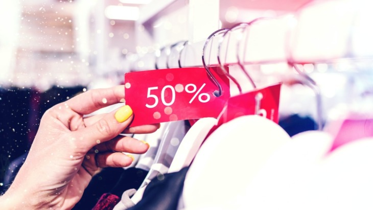 person holding a 50% off sale tag