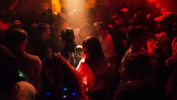 A girl stands amidst others in a club